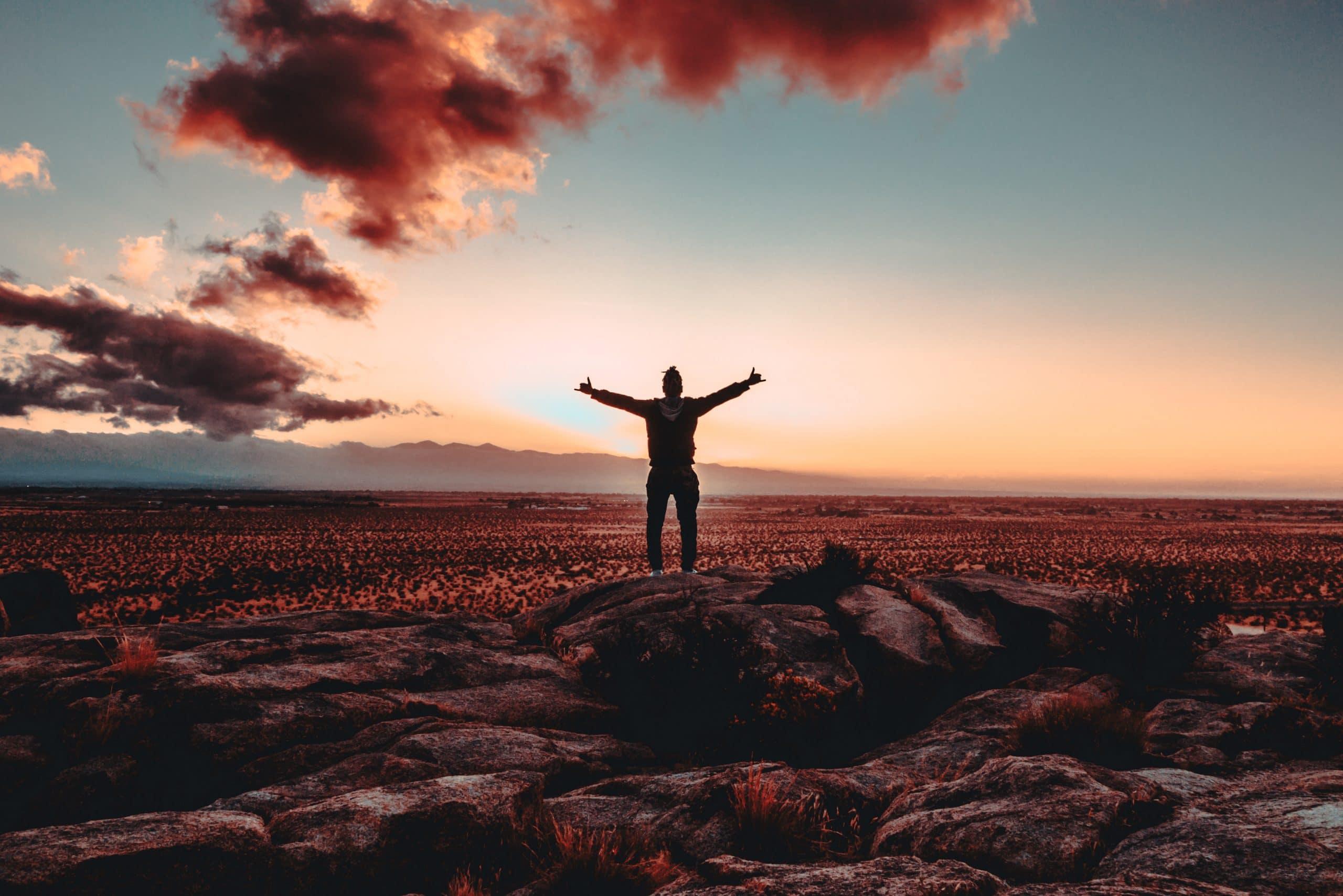 Homem em pedras com braços abertos e céu azul com nuvens e sol ao fundo