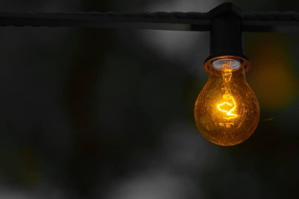 Lâmpada acesa em meio a um ambiente escuro.