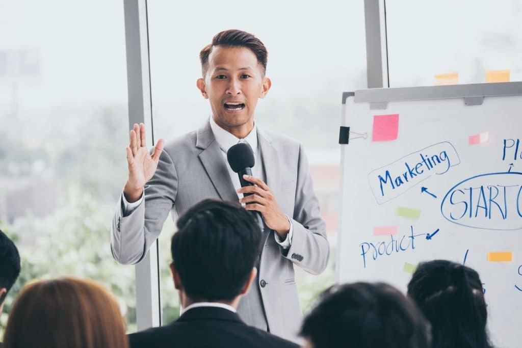 Homem asiático falando em um microfone.