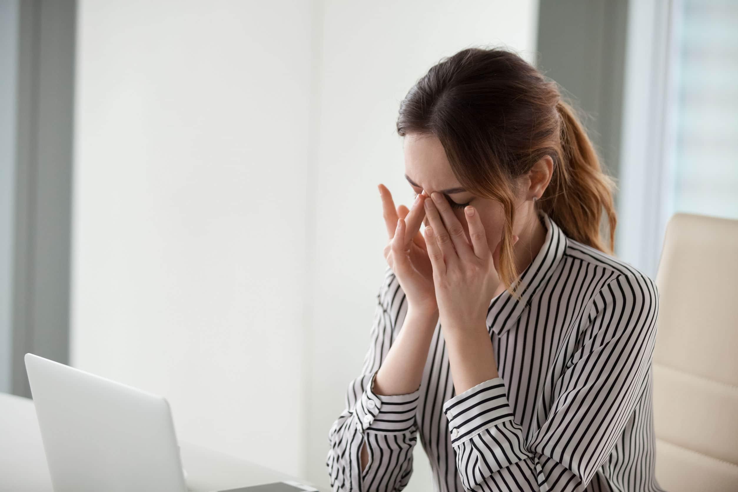 Mulher sentada na mesa de trabalho com os olhos fechados e cabeça abaixada.