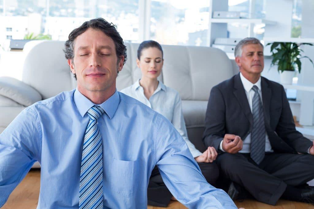 Dois homens e uma mulher com roupas sociais praticando yoga em uma sala de escritório.