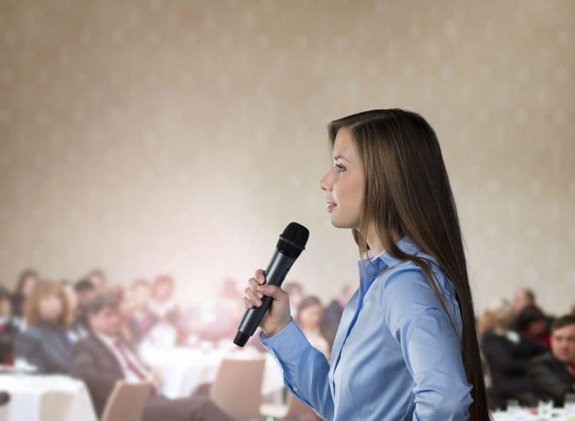 Mulher de pele branca e cabelos lisos segurando um microfone e falando para pessoas que estão sentadas.