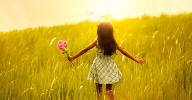 Garota pequena com os cabelos escuros e um veztido zadrez de cor branca e verde de costas correndo sobre as gramas sentido o pôr do sol,.