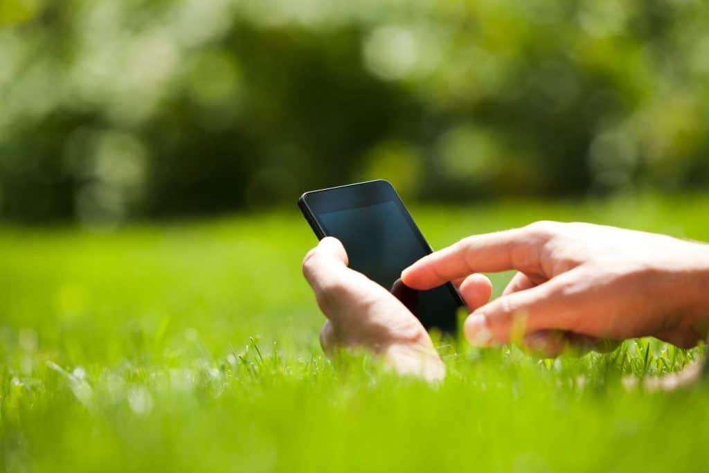 Cenário com gramado e árvores verdes ao fundo. No centro da imagem, há uma mão humana segurando um celular.