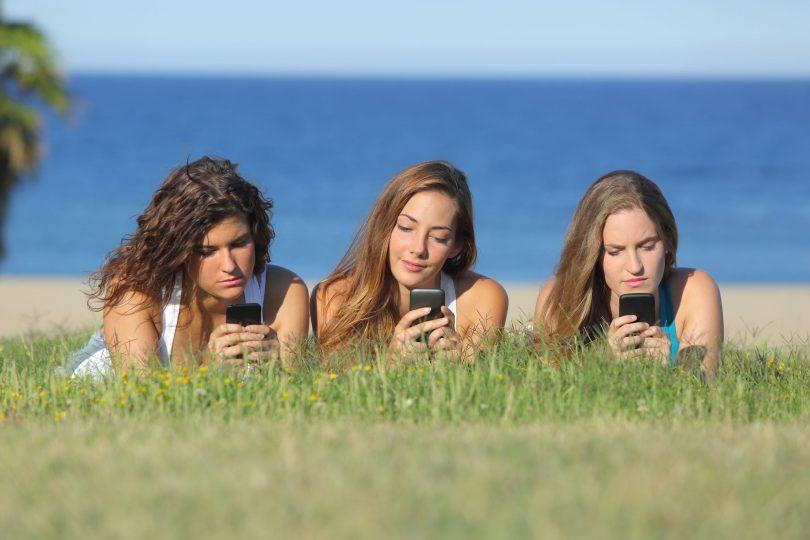Três amigas mexendo no celular.