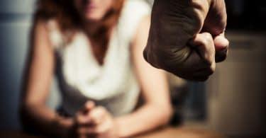 Mulher na frente de homem com punhos cerrados.