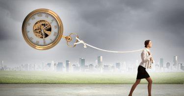 Uma mulher com saia preta e camisa branca anda para frente segurando uma corda onde há um grande relógio amarrado.