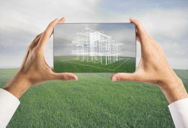 Mão humana segurando um projeto de arquitetura desenhado sob grama verde.