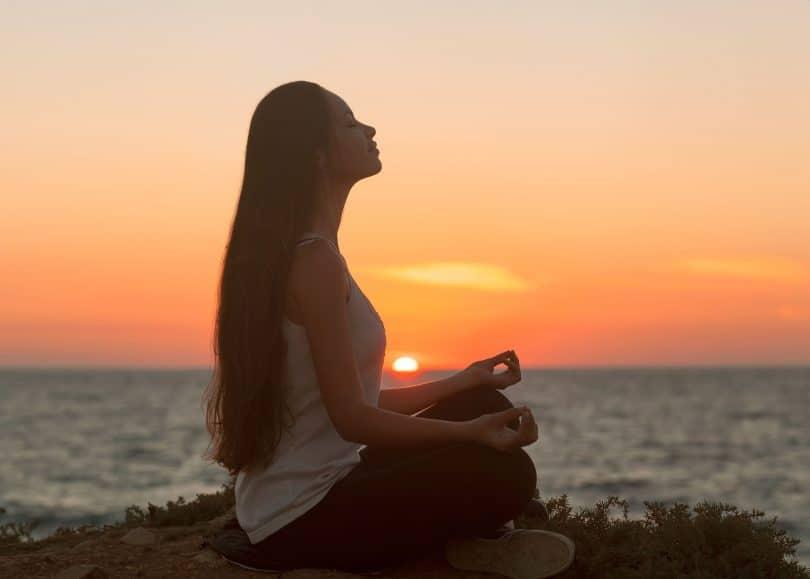 Mulher meditando sob montanha com mar e sol se pondo ao fundo