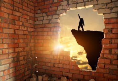 Uma parede de tijolos laranjas com um grande buraco. Dentro do buraco, é possível ver um homem num topo de um penhasco com o punho para cima.