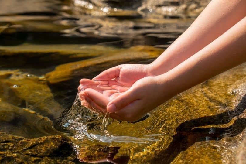 Água de fonte sobre duas mãos.