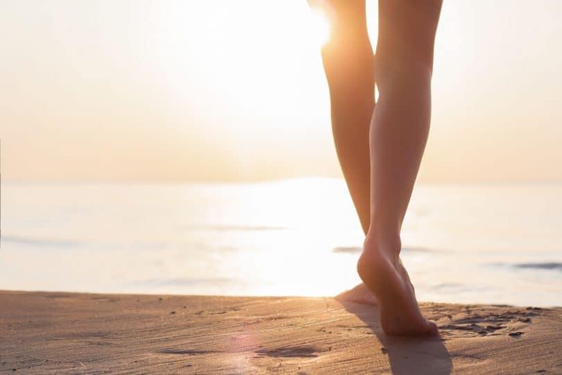 Pés caminhando na areia sentido mar com sol refletindo ao fundo