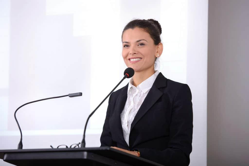 Mulher sorridente falando em um microfone.