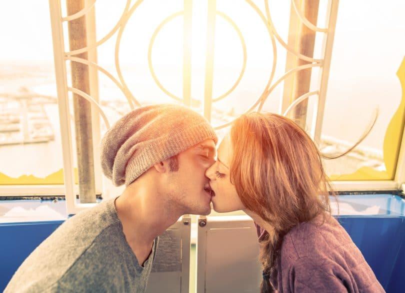 Casal de jovens se beijando em frente a uma janela.