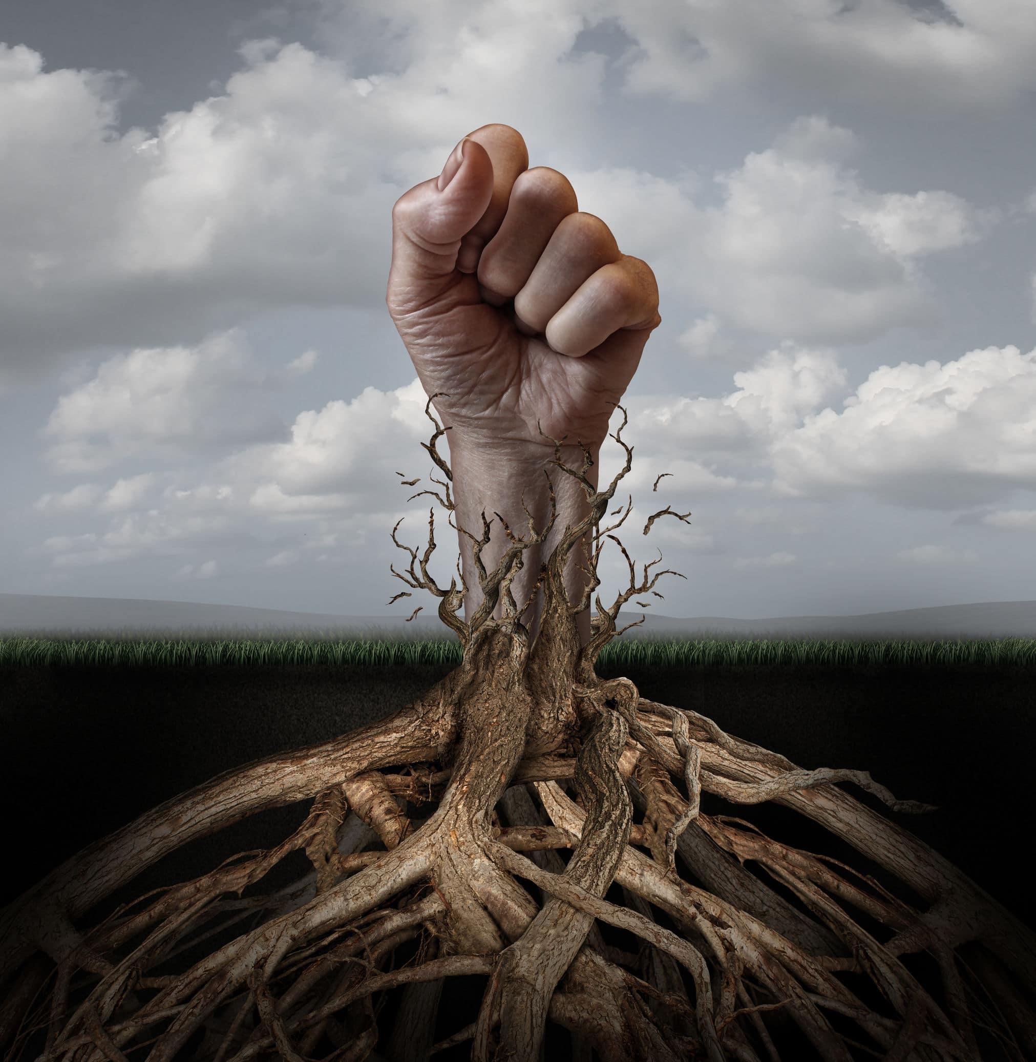 Um punho fechado de uma mão humana brotando do chão como se fosse uma árvore crescendo das raízes.