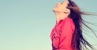 Mulher sorrindo com cabelos ao vento e céu azul ao fundo