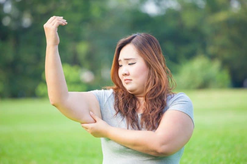 Mulher asiática apertando o braço