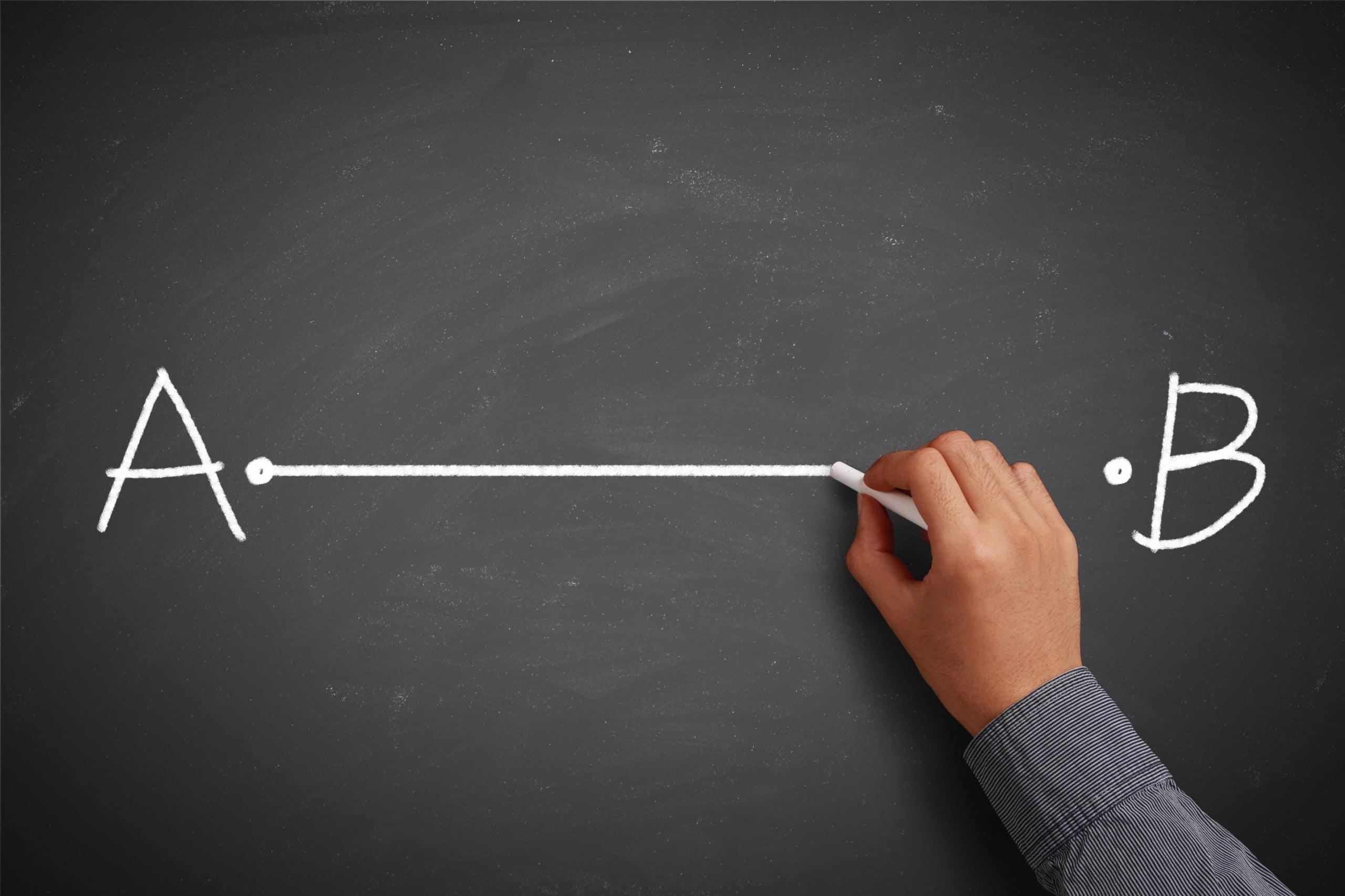 Mão traçando uma linha entre o ponto A e B em uma lousa.