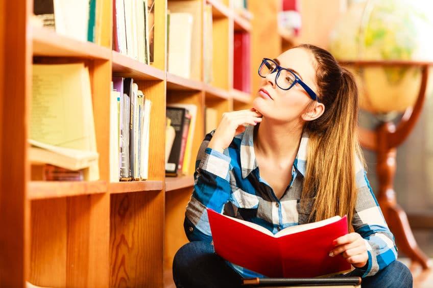 Garota olhando para livros na estante