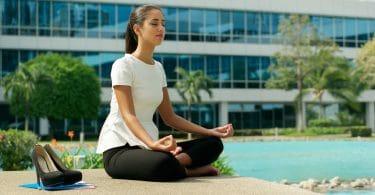 Mulher de negócios praticando yoga perto de prédio comercial.