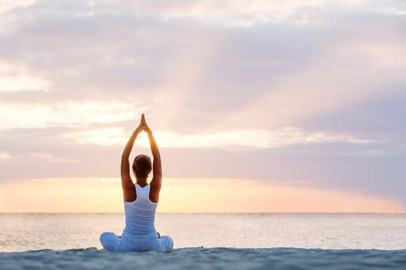 Mulher praticando yoga na beira da praia.