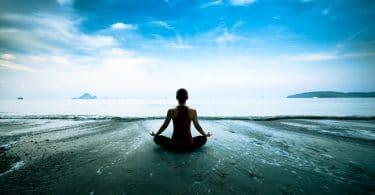 Silhueta de uma jovem mulher praticando yoga na praia.