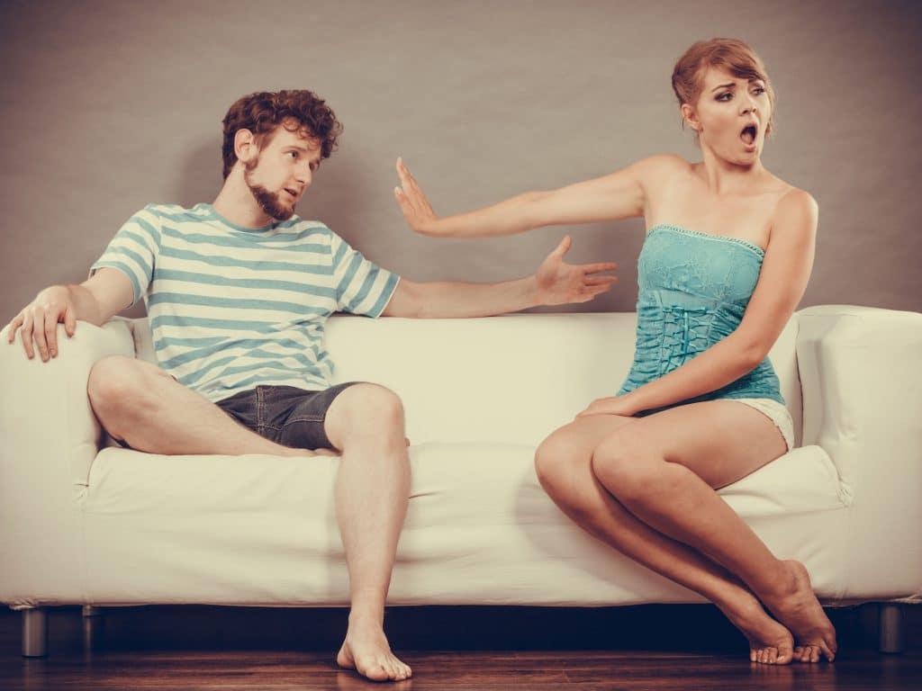 Homem e mulher sentados em um sofá branco, discutindo