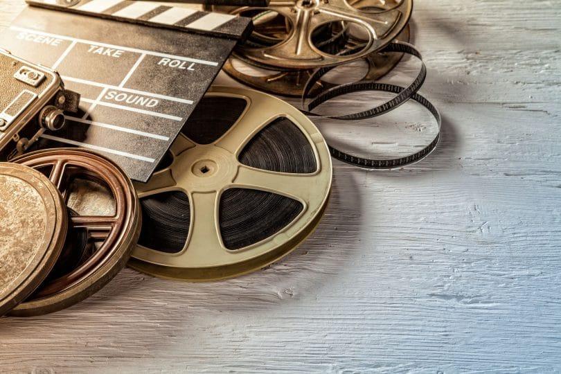 Rolos e claquetes do cinema amontados em uma mesa.