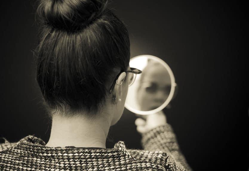 Mulher olhando seu reflexo no espelho