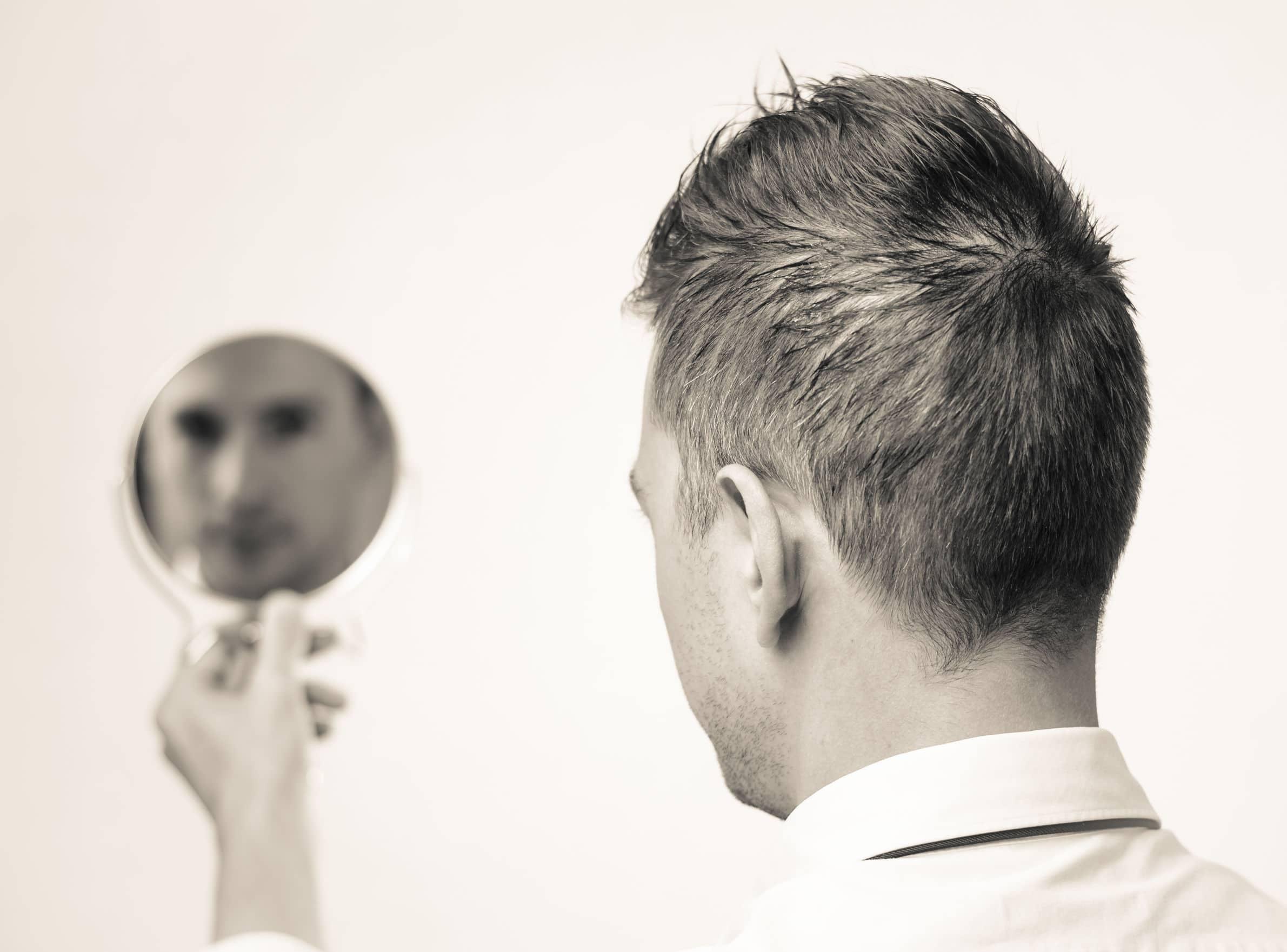 Homem se olhando no espelho.