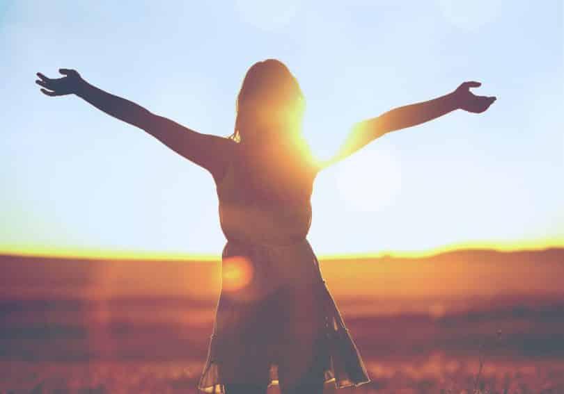 Silhueta de mulher com os braços abertos num campo.
