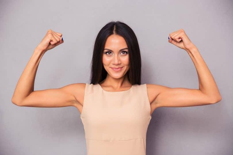 Mulher com braços levantados fazendo sinal de força