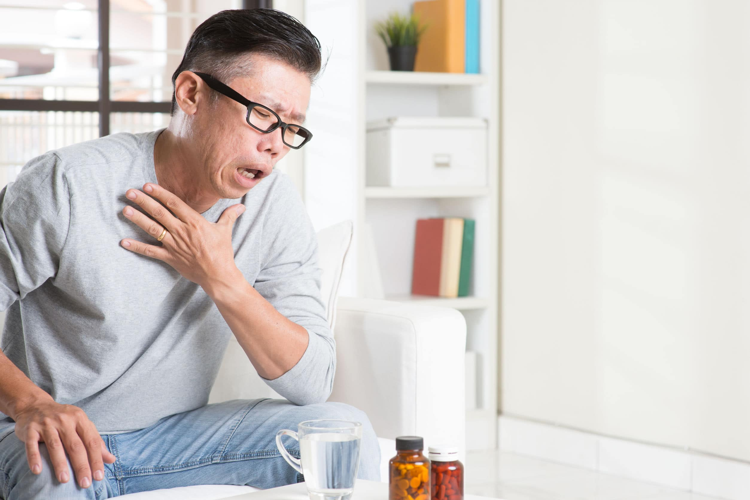 Homem com mão no pescoço sentado com copo de água e remédios sob a mesa