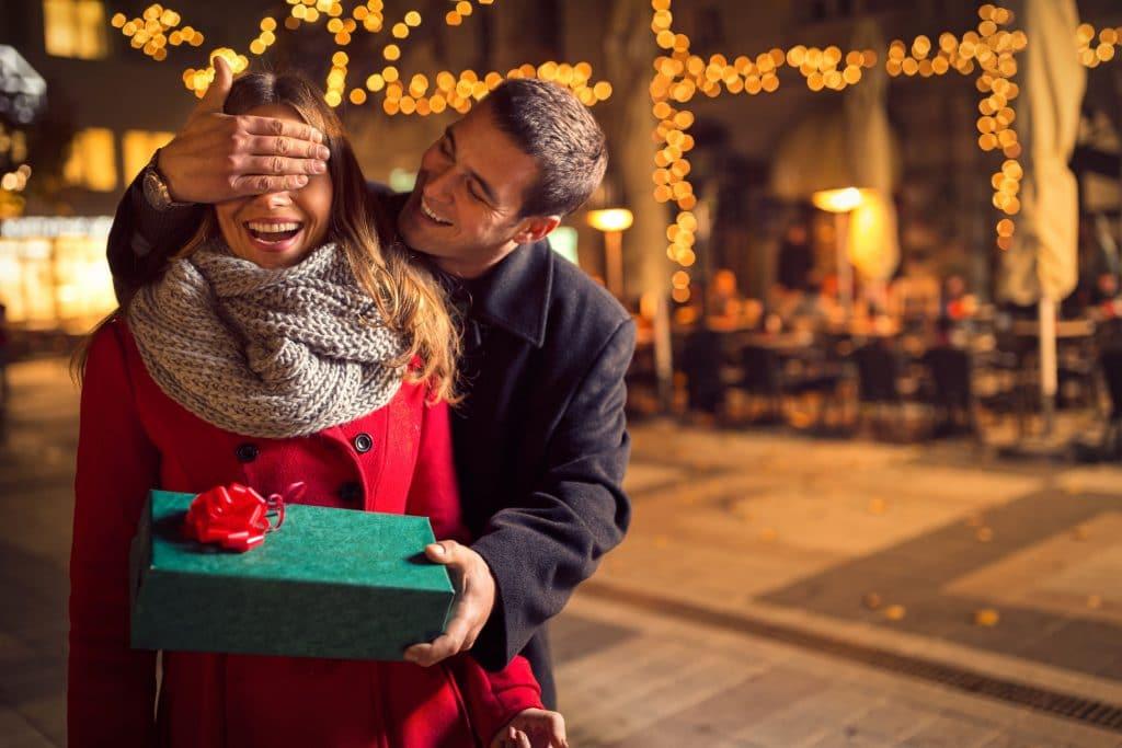 Homem branco surpreendendo sua namorado, cobrindo os olhos dela enquanto entrega um presente