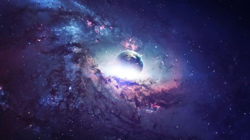 Planeta Terra envolto por uma nebulosa estrelada em tons de azul e roxo.