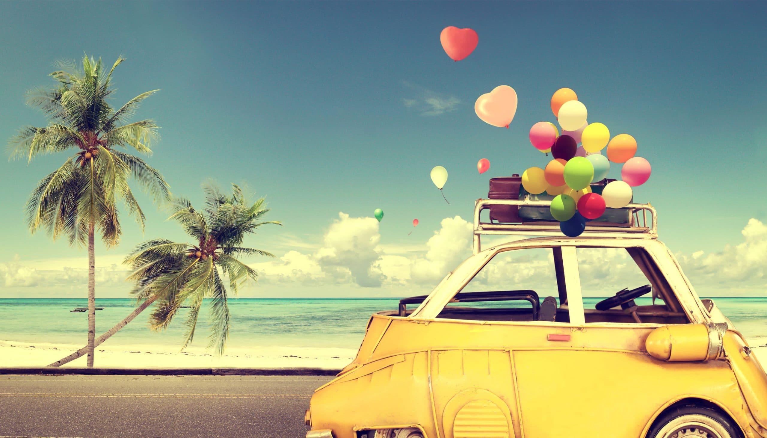 Carro amarelo andando na orla de uma praia, em cima dele, há algumas pequenas bagagens e balões coloridos voando conforme o vento.
