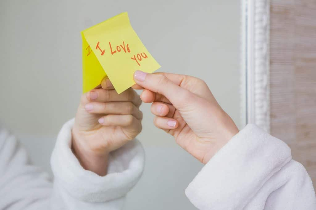 Mão feminina arrancando post it de espelho, que contém o escrito eu te amo, em inglês.