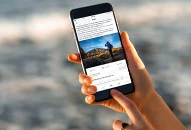 Mãos segurando smartphone aberto em feed facebook