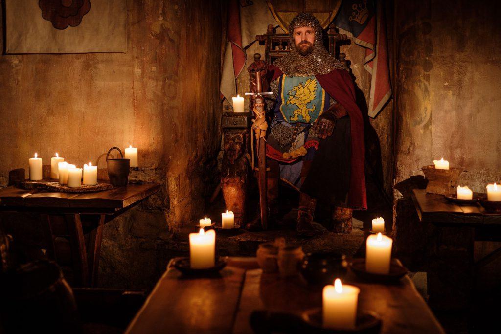 Homem vestido de rei, sentado em um trono, segurando uma espada