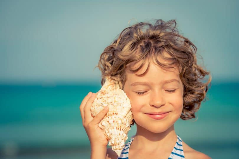 Menina sorrindo e ouvindo concha do mar na praia.