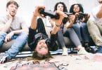 Quatro amigos jovens sentados em um sofá, três deles estão segurando um controle de videogame.