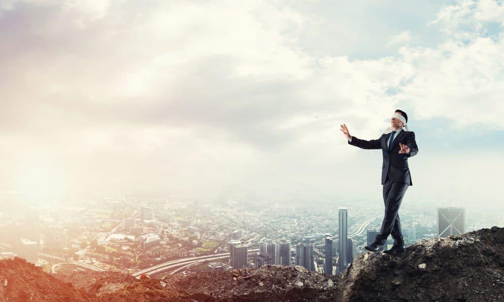 Um homem vestido com roupa social anda sobre o topo de uma montanha com os olhos vendados. Ao fundo, há a imagem de uma cidade vista do alto.