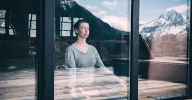 Mulher meditando vista do lado de fora de vidro