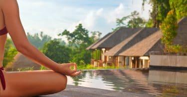 Mulher sentada praticando yoga em frente a duas casas cercadas pela natureza e por uma piscina.