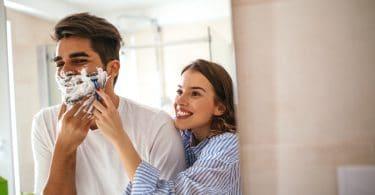 Casal brinca e dá risada enquanto o homem faz a barba.