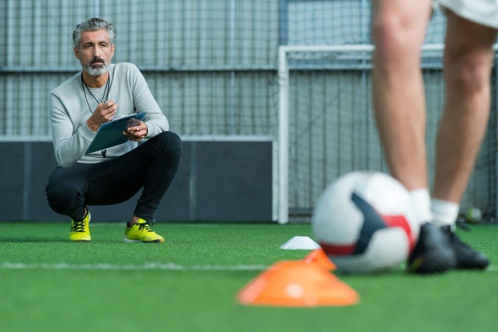Homem, técnico de futebol, agachado no campo, segurando uma prancheta enquanto observa outro homem jogar