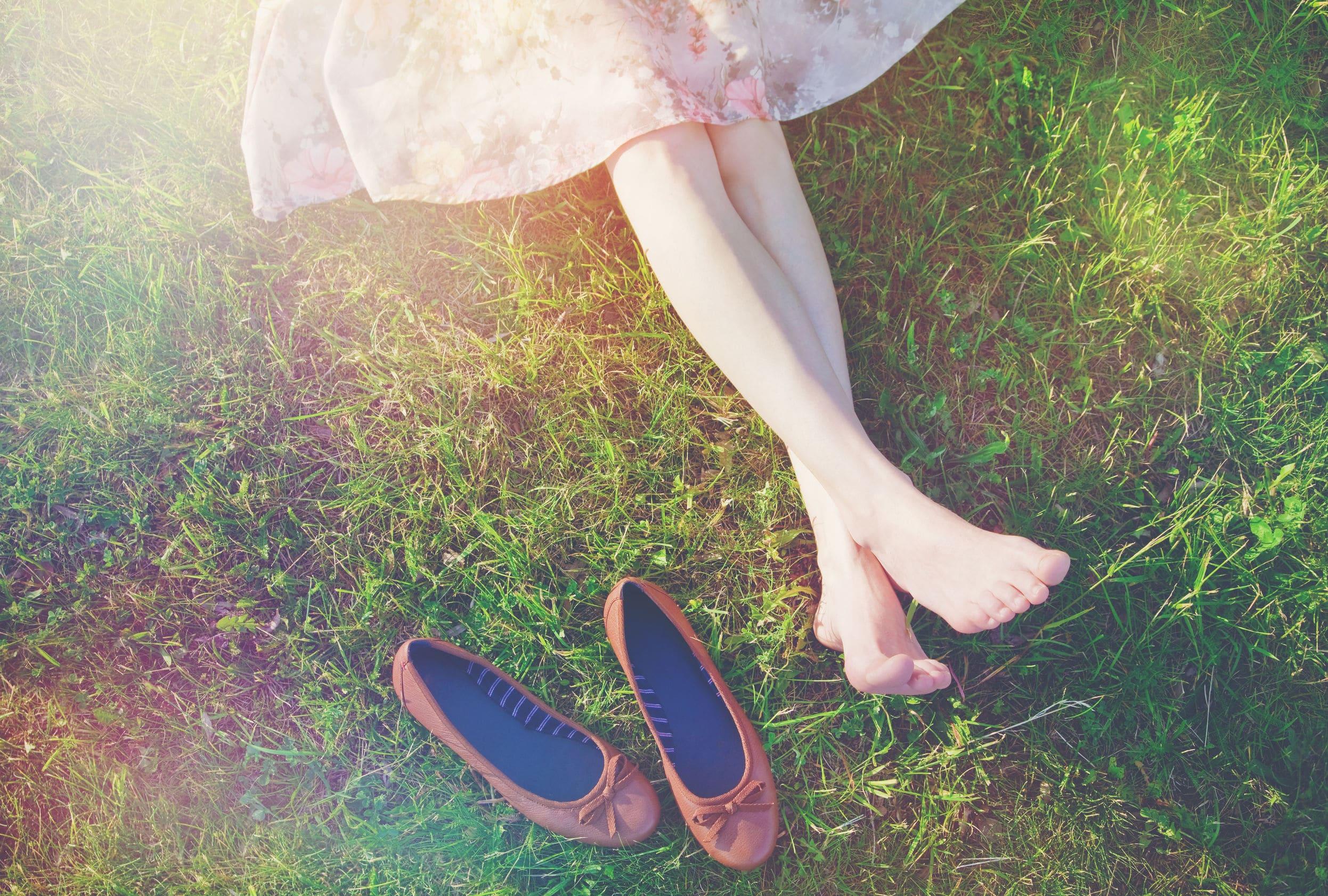 Pernas de uma menina deitada no gramado de pés descalços e um pedaço do vestido rosa florido a mostra. Ao lado, está seu par de sapatilhas vermelhas.