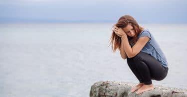 Mulher agachada em pedra