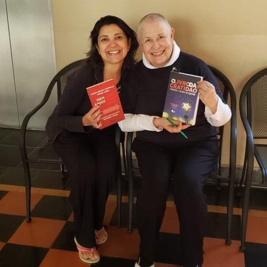 Autora e Monja Coen com livros nas mãos. Ambas sorriem.