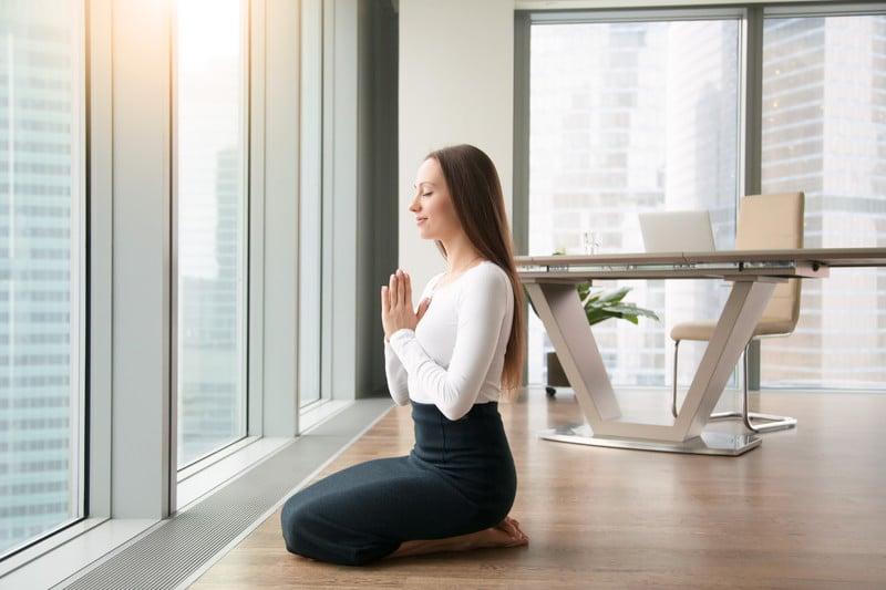 Mulher sentada sobre as pernas com as mãos em oração olhando para fora da janela do escritório.